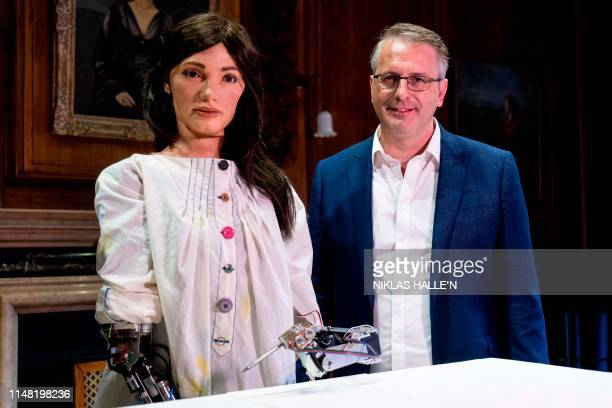 Gallery Director and inventor of AiDa the AI humanoid robot artist Aidan Meller poses with AiDa during a launch event for its first solo exhibition...