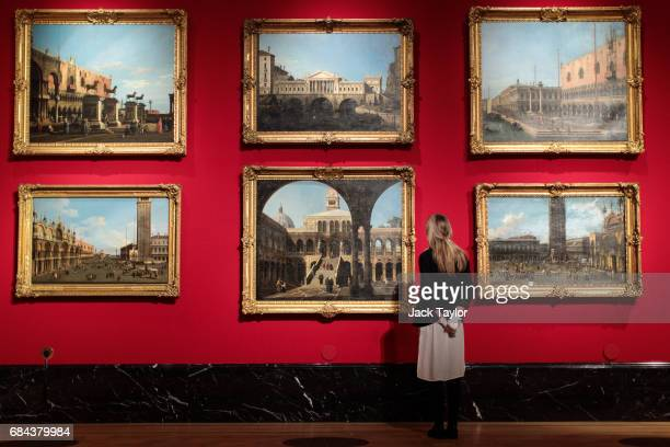 A gallery employee poses with a series of Overdoors depicting views of Venice painted from 17421744 by Canaletto at The Queen's Gallery at Buckingham...