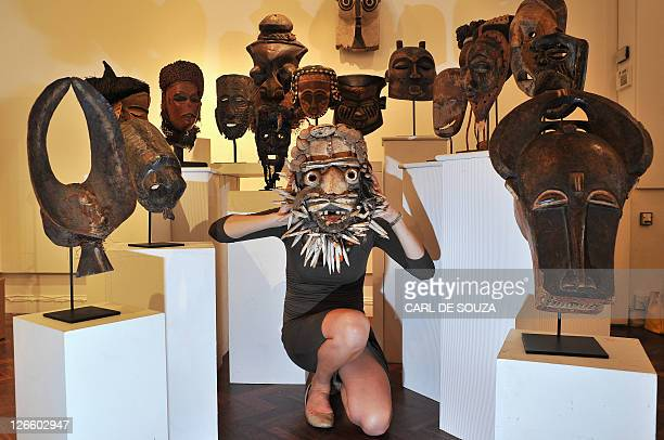 Gallery Manager Anna BurdonCooper poses with an Ivorian Dan Gere African tribal mask during a photocall for the 'Tribal Perspectives' exhibition at...