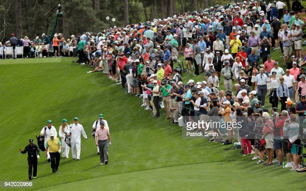 A gallery of patrons look on as Gary Player of South Africa Tom Watson of the United States and Jack Nicklaus of the United States walk together...