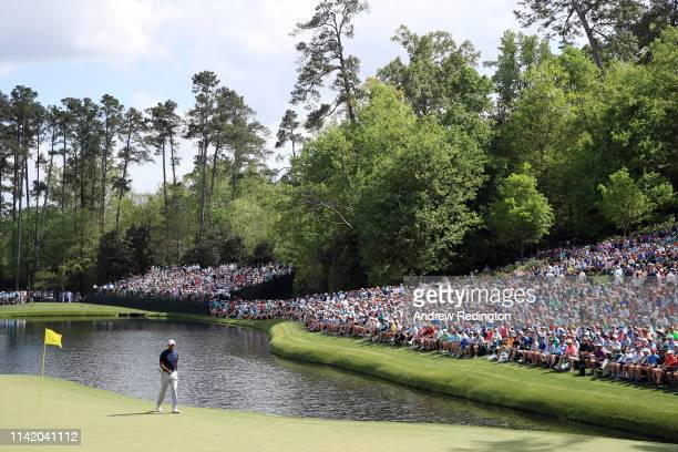 Gallery of patrons look on while Tiger Woods of the United States walks across the 16th green during the first round of the Masters at Augusta...