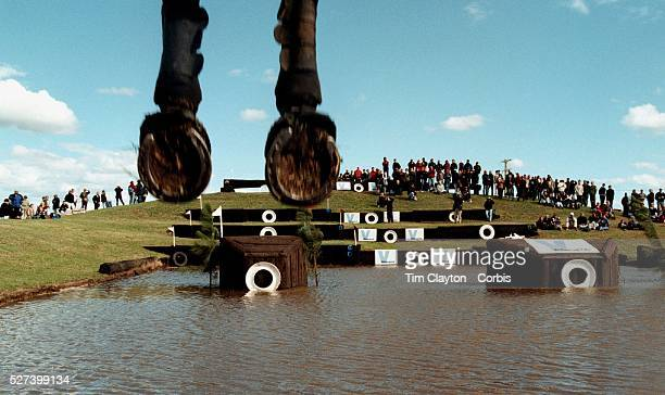 A gallery of spectators surround the water jump as a horses hooves appear over the jump at Lochinvar during an equestrian three day event Photo Tim...