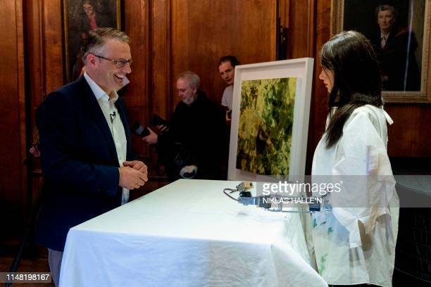 Gallery owner and creator Aidan Meller talks to Ai-Da the AI humanoid robot artist as it draws a portrait of him during a demonstration at a launch...