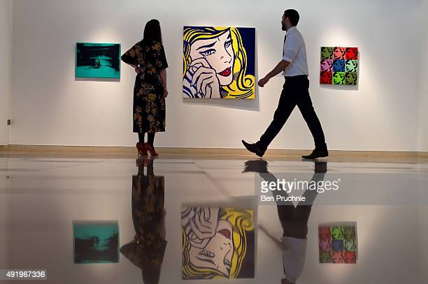 Gallery staff look at 'Crying Girl' by artist Roy Lichtenstein during the preview ahead of the artist's muse a curated evening sale at Christie's New...