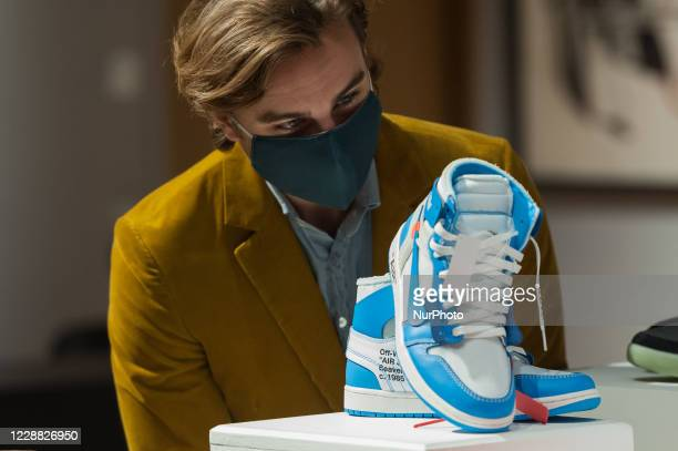 Gallery staff member looks at A pair of off-white X Nike Air Jordan 1 UNC 'Revealing' during a photo call for Bonhams' Pop x Culture sale, on October...