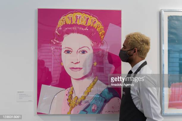 Gallery staff member looks at 'Queen Elizabeth II', from: Reigning Queens screenprint in colours by Andy Warhol , estimate: £100,000 - 150,000...
