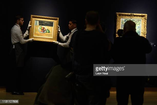 Gallery staff pose for photographers with 'Nature morte de peches et poires' by Paul Cezanne during a press preview of the 'Impressionist and Modern...