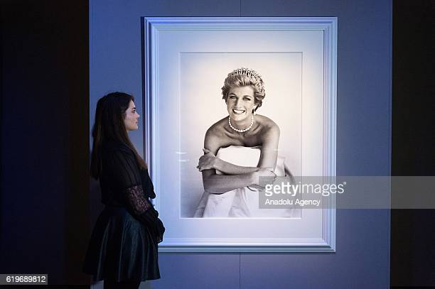 Gallery staff views a photographer of Diana Princess of Wales for British Vogue December 1990 by photographer Patrick Demarchelier at the exhibition...