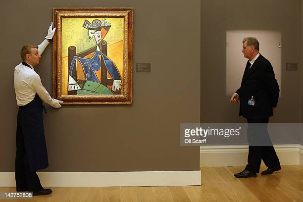 A gallery technician at Sotheby's auction house adjusts a portrait of Dora Maar entitled 'Femme assise dans un fauteuil' by Pablo Picasso which is...