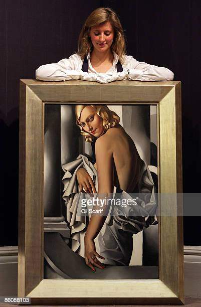 A gallery technician at Sotheby's auction house admires a painting by Tamara de Lempicka entitled 'Portrait de Marjorie Ferry' from 1932 which is...