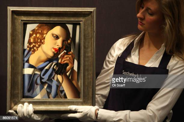 A gallery technician at Sotheby's auction house admires a painting by Tamara de Lempicka entitled 'Le Telephone II' from 1930 which is expected to...