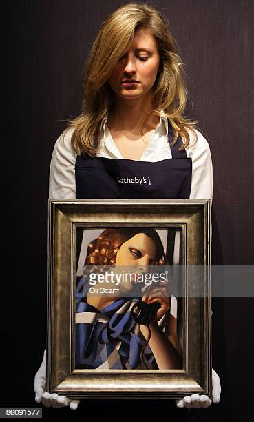 A gallery technician at Sotheby's auction house holds a painting by Tamara de Lempicka entitled 'Le Telephone II' from 1930 which is expected to...