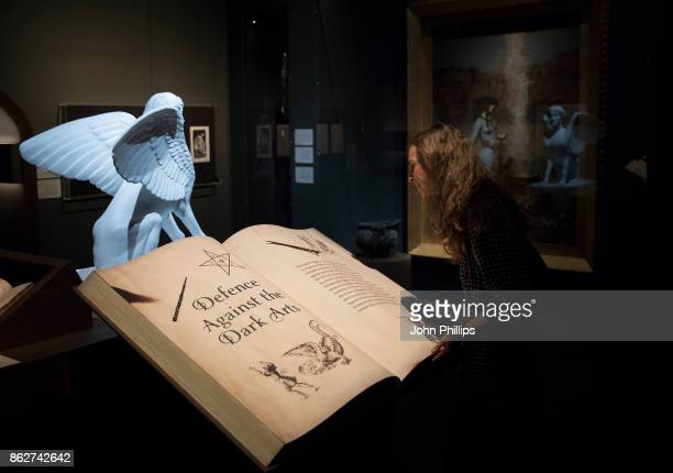 A gallery technician poses for photographers during a press Preview of the 'Harry Potter A History of Magic' exhibition at The British Library on...