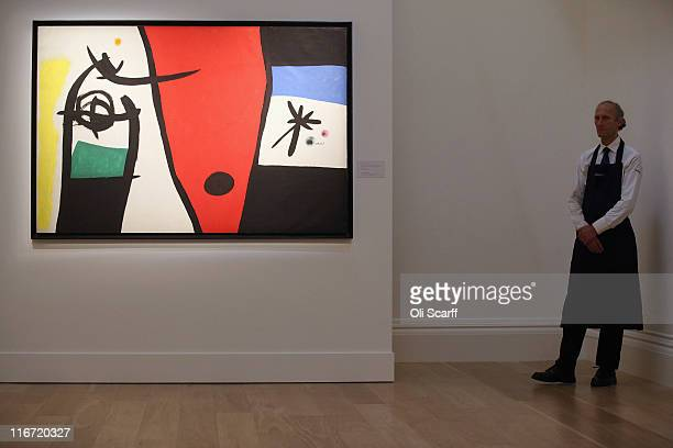 A gallery technician stands next to a painting by Joan Miro entitled Femme a la voix de rossignol dans la nuit in Sotheby's auction house on June 17...