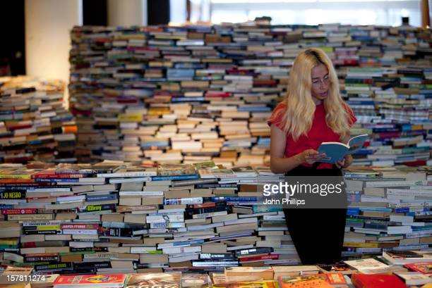 Gallery Technician Tilly Shiner Reads One Of The Books From A Labyrinth Of 250000 Books Entitled Amazeme Is Installed On The Clore Ballroom In The...