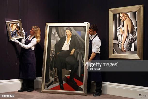 Gallery technicians at Sotheby's auction house adjust paintings by Tamara de Lempicka entitled 'Portrait de la Duchesse de la Salle' from 1925 and...