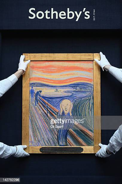 Gallery technicians at Sotheby's auction house hold up 'The Scream' by Edvard Munch on April 12 2012 in London England The iconic painting is on...