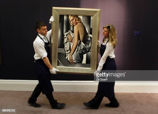 Gallery technicians at Sotheby's auction house lift a painting by Tamara de Lempicka entitled 'Portrait de Marjorie Ferry' from 1932 which is...