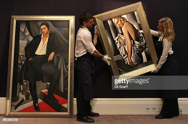 Gallery technicians at Sotheby's auction house lift a painting by Tamara de Lempicka entitled 'Portrait de Marjorie Ferry' from 1932 next to another...