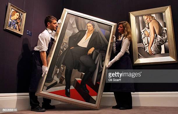 Gallery technicians at Sotheby's auction house lift a painting by Tamara de Lempicka entitled 'Portrait de la Duchesse de la Salle' from 1925 next to...