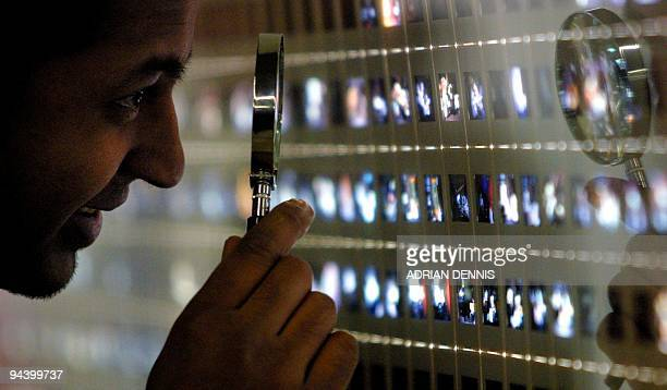 A gallery visitor takes a closer look at 35mm film transparencies during the press preview of Century City Art and Culture in the Modern Metropolis...