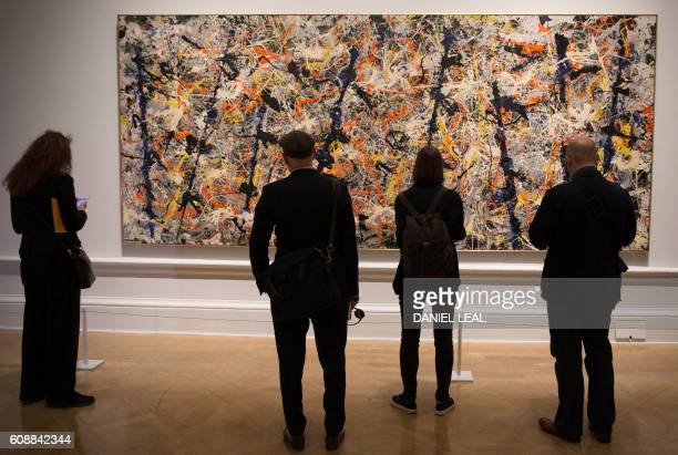 Gallery visitors stand in front of a painting entitled 'Blue Poles' by US artist Jackson Pollock during a photocall to promote Abstract Expressionism...