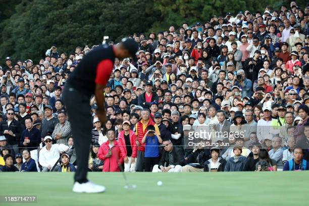 Gallery watch Tiger Woods of the United States putting on the 9th green during the final round of the Zozo Championship at Accordia Golf Narashino...