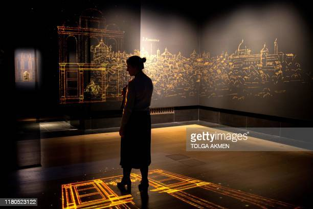 A gallery worker poses with a projection of an imagined chapel during a photocall for the upcoming 'Leonardo Experience a Masterpiece' exhibition at...