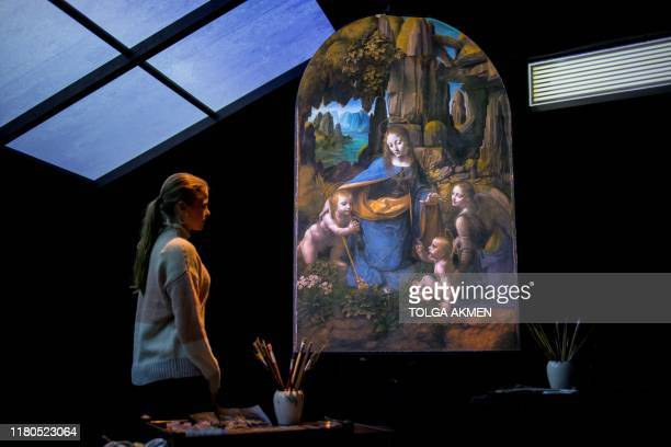 A gallery worker poses with a projection of the painting 'The Virgin of the Rocks' by Leonardo da Vinci in a reimagined studio room during a...