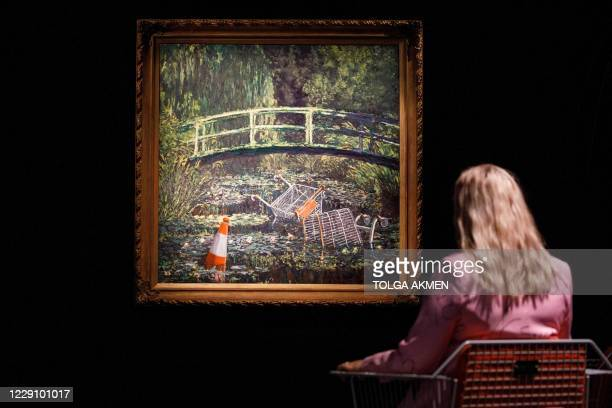 Gallery worker poses with an artwork entitled Show me the Monet by British street artist Banksy during a photo call for Major Contemporary Art...