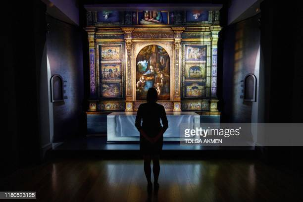 A gallery worker poses with the painting 'The Virgin of the Rocks' by Leonardo da Vinci during a photocall for the upcoming 'Leonardo Experience a...