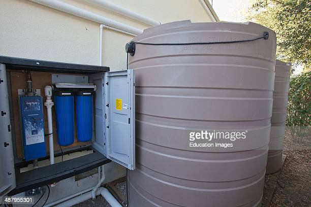865 gallon rain barrel next to UV water filter and micron filters for harvested rainwater on a Green home that is off the grid Solar power and a...