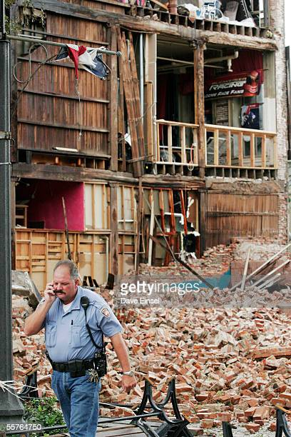 Galveston police officer Lewis Trochesset talks with the owner of the historic Greenleve Block Company Building after the east wall collapsed during...
