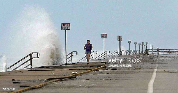 The walls of Seawall Boulevard are lashed by waves as John McKenna jogs 23 September 2005 in Galveston Texas ahead of Hurricane Rita McKenna tried to...