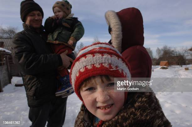 Galya Molchanovich with rotten teeth and bobble hat with her father and siblings in the snow outside their home in Rivne 500km west of Chernobyl down...