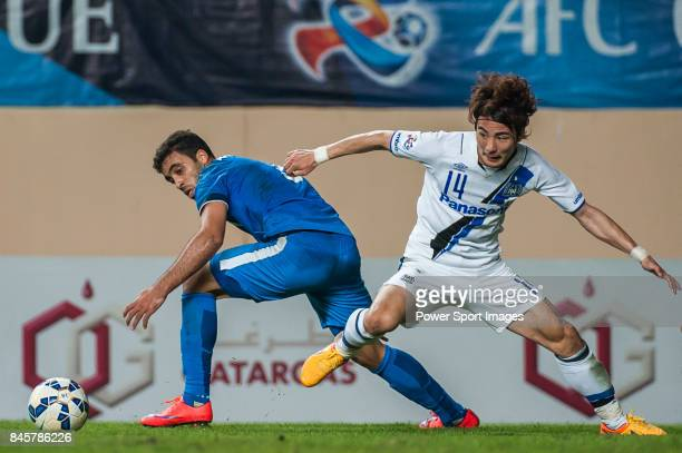 Gamba Osaka defender Yonekura Koki fights for the ball with Guangzhou RF forward HamedAllah Abderrazzaq during the 2015 AFC Champions League Group...