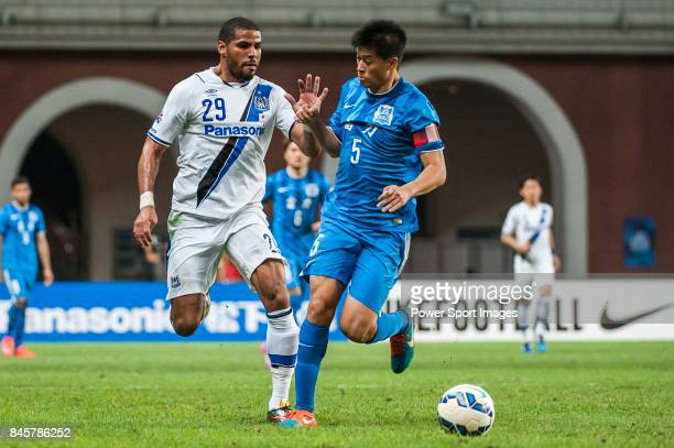 Gamba Osaka forward Anderson Patric Aguiar Oliveira fights for the ball with Guangzhou R&F defender Zhang Yaokun during the 2015 AFC Champions League...