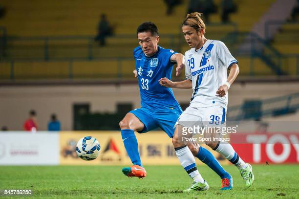 Gamba Osaka forward Usami Takashi fights for the ball with Guangzhou RF midfielder Li Yan during the 2015 AFC Champions League Group Stage F match...