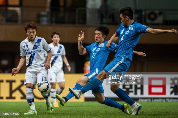 Gamba Osaka midfielder Abe Hiroyuki fights for the ball with Guangzhou RF defender Jiang Zhipeng and Guangzhou RF defender Jin Yangyang during the...