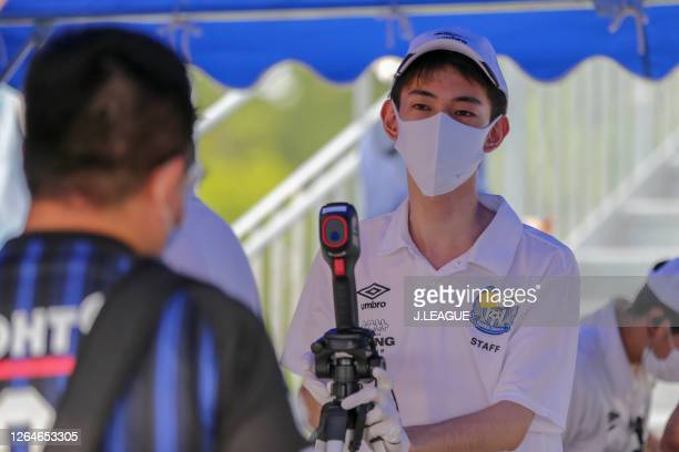 Gamba Osaka staff uses a thermography to check people's temperature on arrival at the stadium prior to the J.League Meiji Yasuda J1 match between...