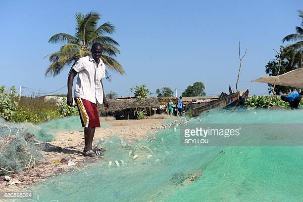 Gambian Ansu Sanyang prepares the fishing nets on the beach in the village of Sanyang on December 4 2016 Ansu Sanyang was ready Sick of providing so...