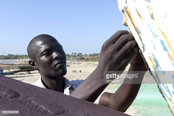 Gambian Ansu Sanyang repairs a dugout on the beach in the village of Sanyang on December 4 2016 Ansu Sanyang was ready Sick of providing so little...