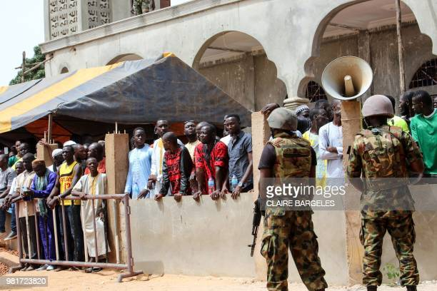 Gambian men from the village of Faraba Banta wait at the entrance of the local mosque in Faraba Banta during the speech of the Gambian president on...