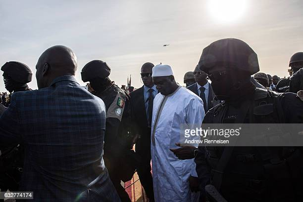Gambian President Adama Barrow is surrounded by security as he arrives at Banjul International Airport on January 26 2017 in Banjul The Gambia Barrow...