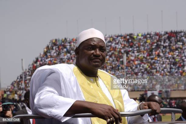 Gambian President Adama Barrow looks at the audience from the opened roof of a car as he arrives at the Independence Stadium in Bakau, west of the...