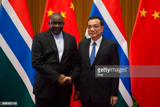 Gambian President Adama Barrow shake hands with China's Premier Li Keqiang at the end of a signing ceremony at the Great Hall of the People on...