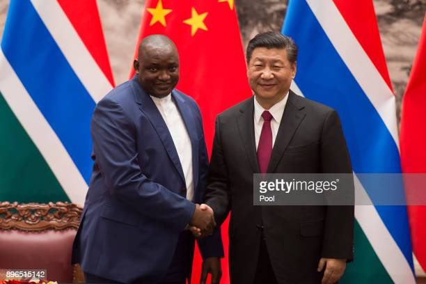 Gambian President Adama Barrow shake hands with Chinese President Xi Jinping at the end of a signing ceremony at the Great Hall of the People on...