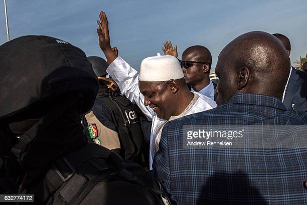 Gambian President Adama Barrow waves as he arrives at Banjul International Airport on January 26 2017 in Banjul The Gambia Barrow had been staying in...