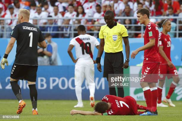 Gambian referee Bakary Gassama speaks with Denmark's midfielder William Kvist as he reacts after being injured during the Russia 2018 World Cup Group...