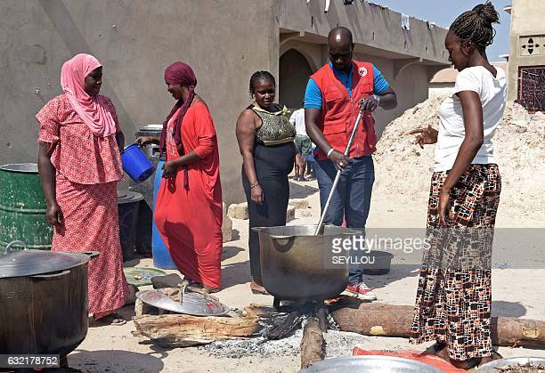 Gambian women refugees are cooking with the help of the Red Cross in a camp in Karang Senegal near the border with Gambia on January 20 2017...